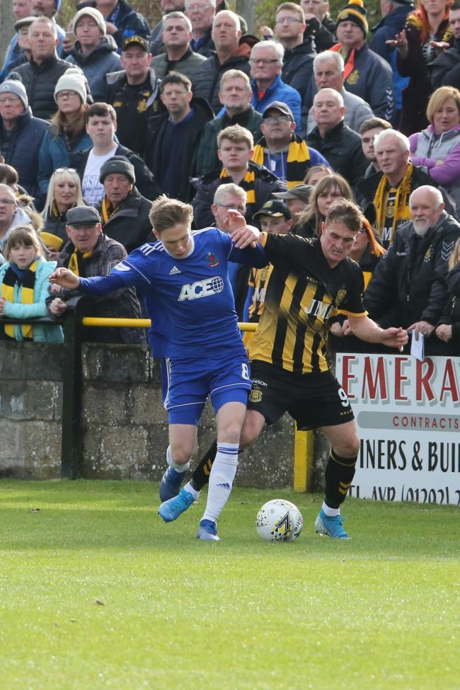 Talbot striker Graham Wilson grapples for the ball.