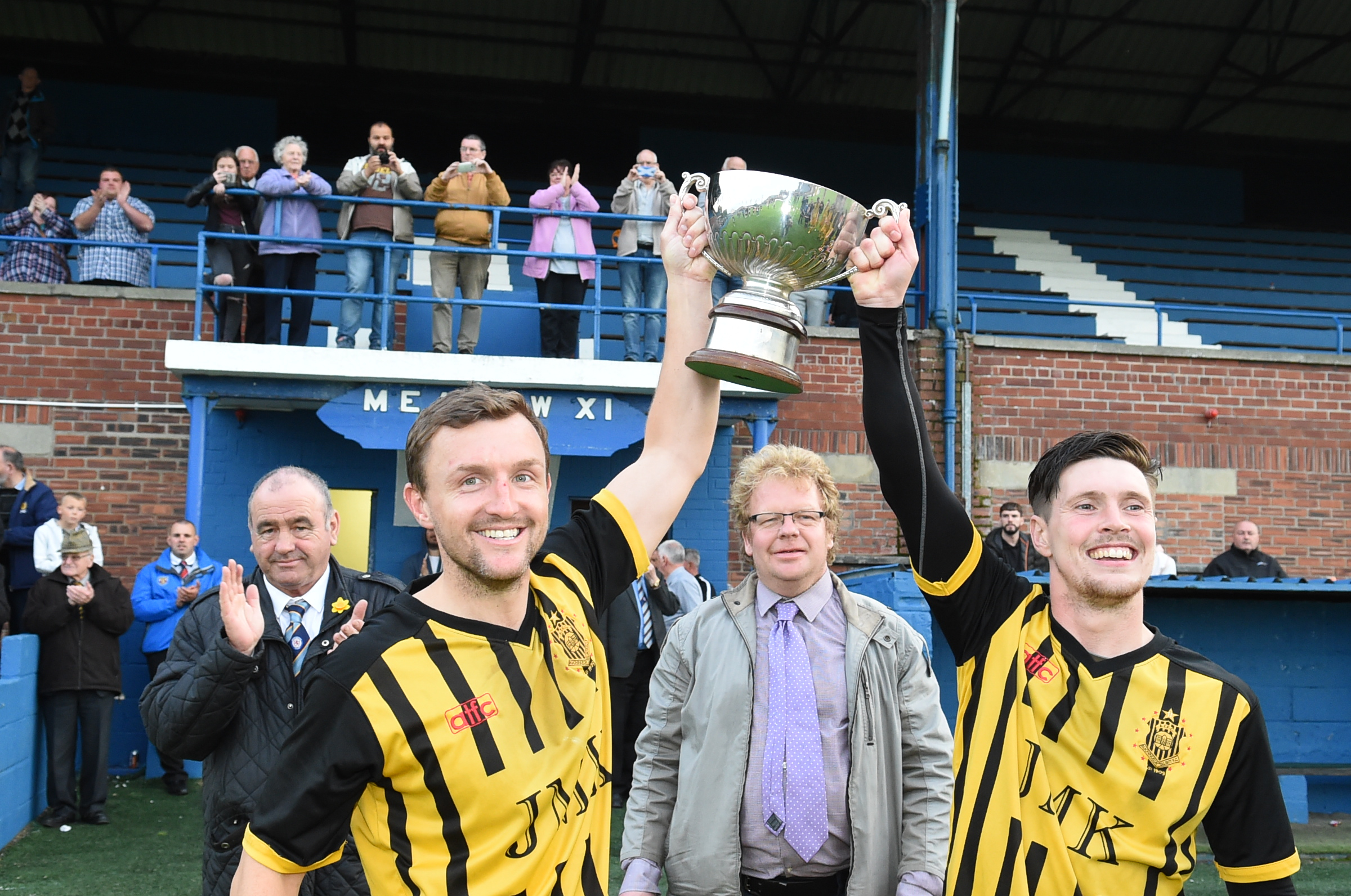 SJFA West Region President Felix McKenna (left) and Ayrshire Weekly Press sports reporter Stewart McConnell (centre right) present James Latta (centre left) and Bryan Young (right) with the trophy.
