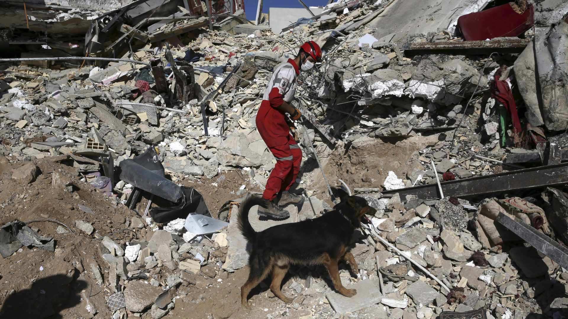 A rescue worker searches the debris with his sniffing dog