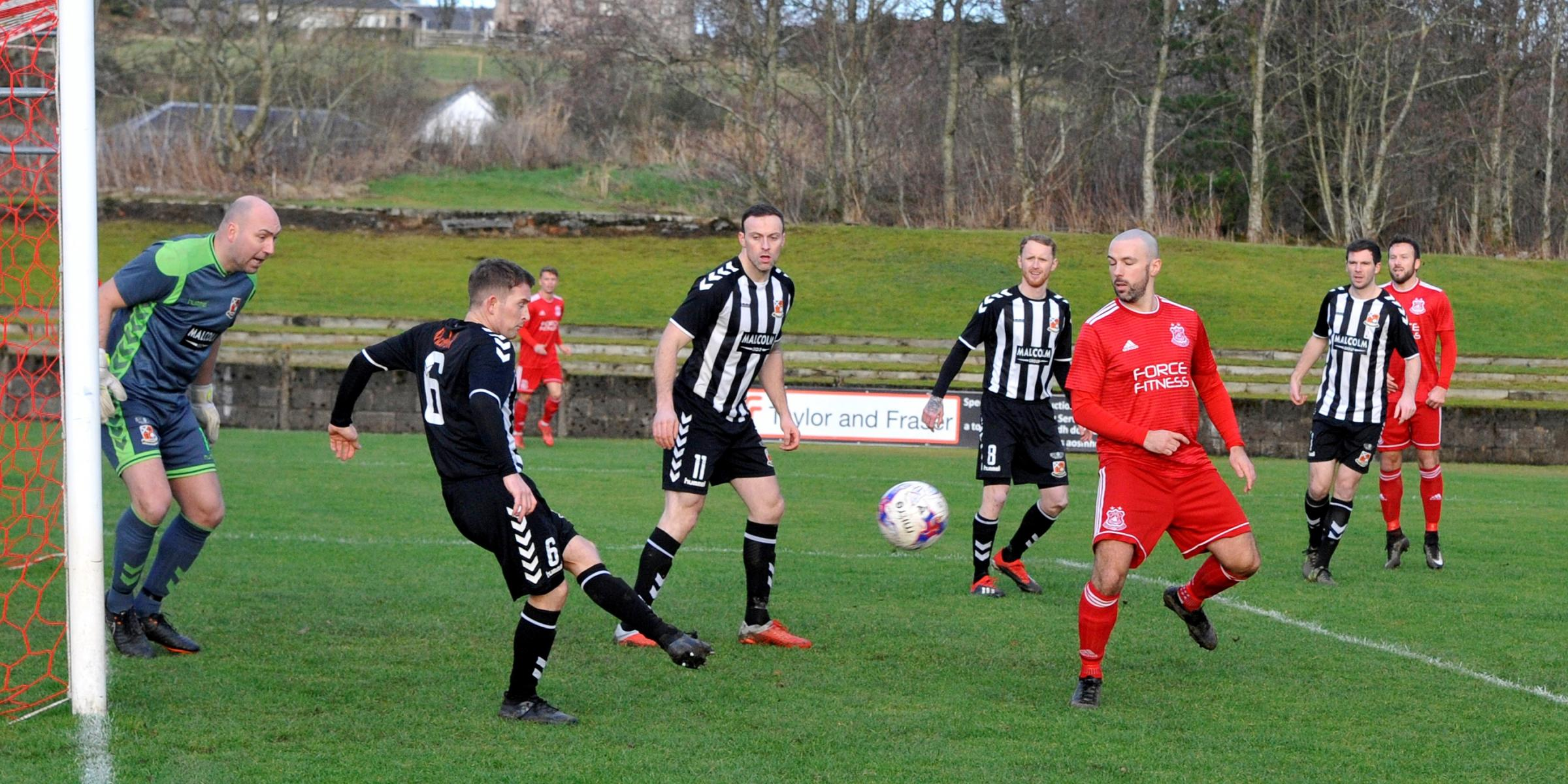 GLENS PRESSURE: Joe Bradley is forced to clear the ball from the six yard box with Joe Andrew lurking against Beith.
